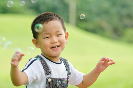 happy asian kid playing soap bubble ,candid  photo