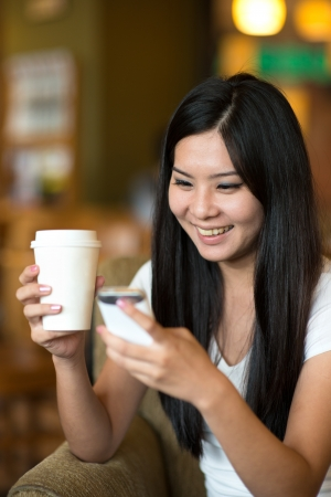 asian flavors: asian woman lifestyle on phone while enjoying coffee