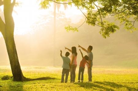 backlit: Una familia asi�tica que apunta a alg�n lugar durante un amanecer hermoso luz de fondo,