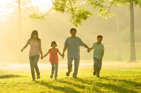 an asian family walking in the park during a beautiful sunrise, backlight photo