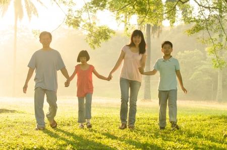 family garden: asian family walking in the park