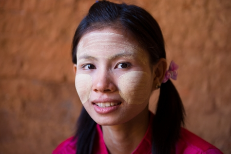 casual myanmar girl on thanaka smiling, close up face photo