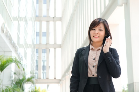 asian business girl using phone at office building photo