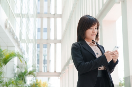 mobile sms: asian business girl using phone at office building Stock Photo