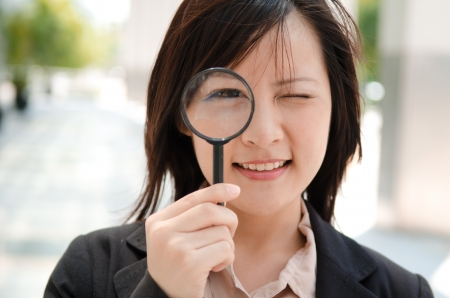 investigate: asian business girl with magnifying glass, smiling
