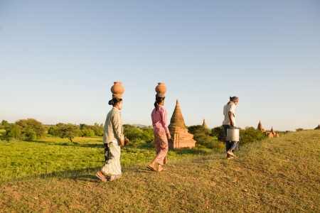 traditional farmers at myanmar, bagan carrying pots back home at bagan photo