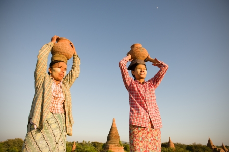 traditional farmers at myanmar, bagan carrying pots photo