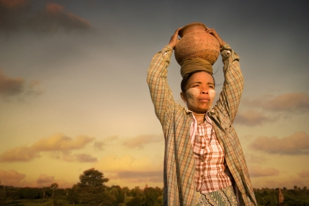 traditional myanmar farmer carrying pot on her head during sunset