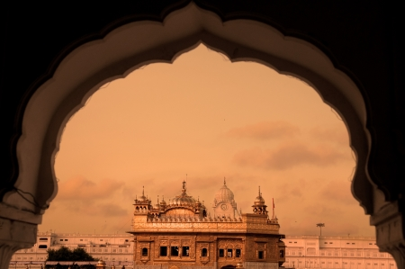 sikh: The Golden Temple of Amritsar - India. Framed with windows from west side. focus on temple