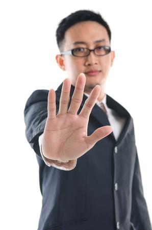 Uomo d'affari serio rendendo il segnale di stop su sfondo bianco. Focus sulla mano