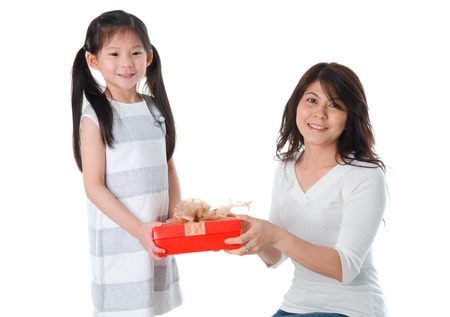 Little Asian girl giving her mother a present during christmas photo