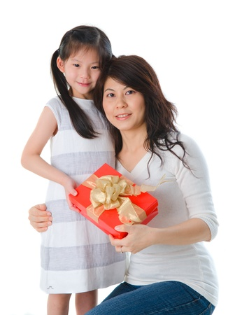 Little Asian girl giving her mother a present during christmas Stock Photo - 16128688