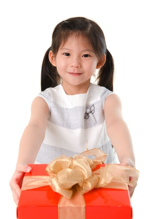 Little Asian girl arms out holding a beautiful wrapped present. Focus is on the girl Stock Photo - 16128690