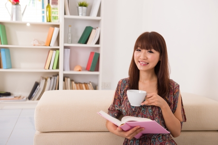 happy asian girl reading on sofa while enjoying coffee Stock Photo - 16252668
