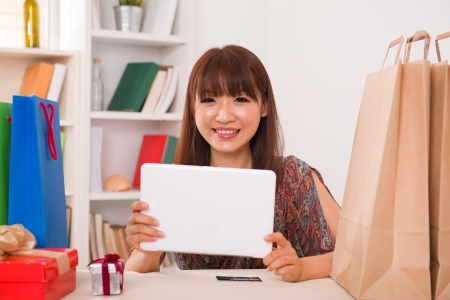 asian girl online shopping with a credit card and generic tablet photo