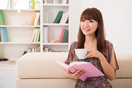 happy asian girl reading on sofa while enjoying coffee  photo