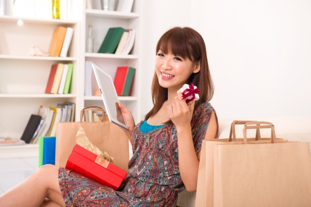 asian girl enjoying online shopping from home, showing off a present  photo