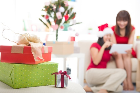 asian christmas friends doing online shopping candid photo,focus on front photo