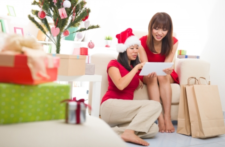 asian christmas friends doing online shopping candid photo,focus on back photo