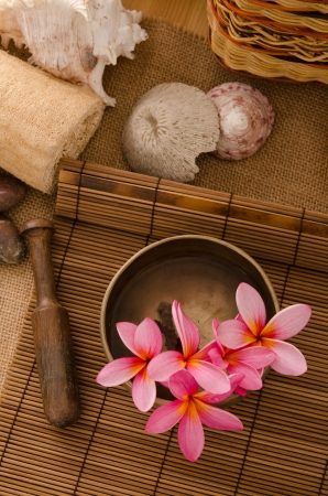photo of tropical spa setup with frangipani flower