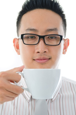 contempory: asian man having tea or coffee break, zoom on face