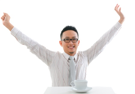 contempory: asian man having tea or coffee break with raised hands