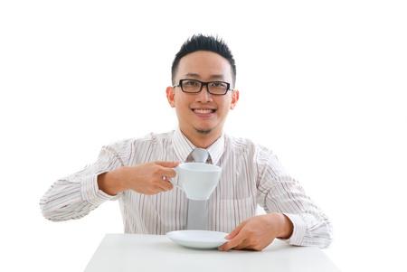 having a break: asian man having tea or coffee break