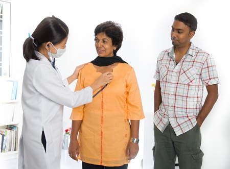 indian senior medical checkup with an asian female doctor photo