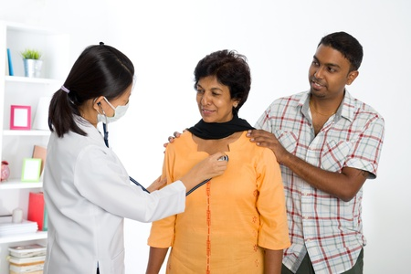 old man on a physical pressure: indian senior medical checkup with an asian female doctor Stock Photo