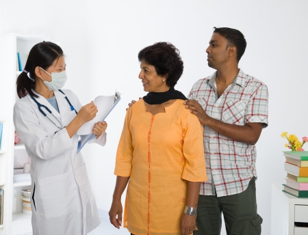 health check: indian senior medical checkup with an asian female doctor Stock Photo
