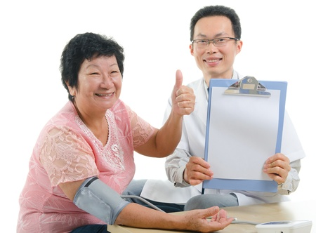 old man on a physical pressure: asian senior female  thumbs up during medical checkup with doctor ,south east asian chinese ethnicity