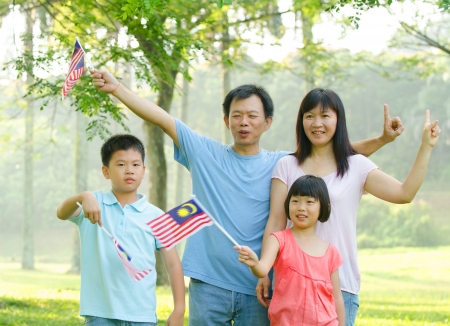 1malaysia: asian family during independence day, holding malaysian flags