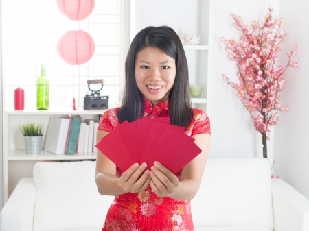 red packet: chinese new year girl with ang pow red packet, with decorations on background