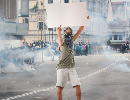 riot: man in street protest with blank cardboard, looks great for advertistment with attitude