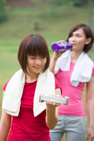 asian girls workout outdoor, a girl is also drinking at the back photo
