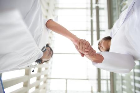 dandose la mano: Dos m�dicos j�venes apret�n de manos, trabajo en equipo