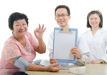 south asian ethnicity: asian senior female thumbs up during medical checkup with doctor ,south east asian chinese ethnicity  Stock Photo