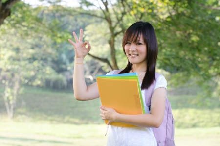asian college student studying outdoor, ok sign  photo