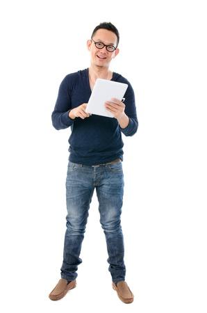 South East Asian Mann mit einer Tablette in casual Stehen