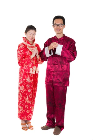 asian couple celebrating chinese new year in traditional clothes and greeting photo