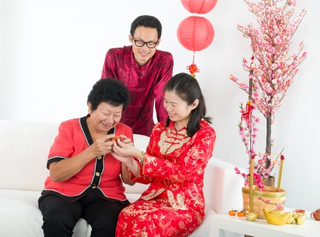 ang: chinese family drinking tea ceremony while celebrating new year
