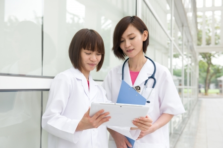 asian female doctors having a meeting with a tablet photo