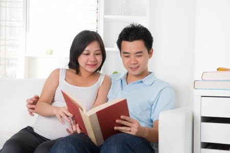 asian chinese pregnant couple reading photo