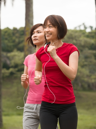 asian girls jogging outdoor while listening to music photo