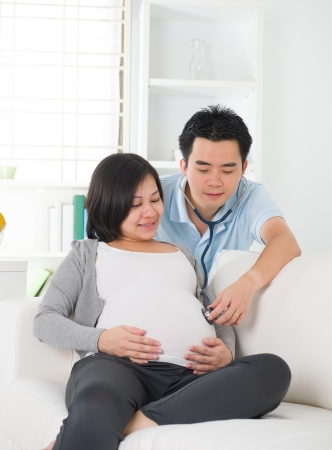 chinese husband listening to his wife's stomach photo