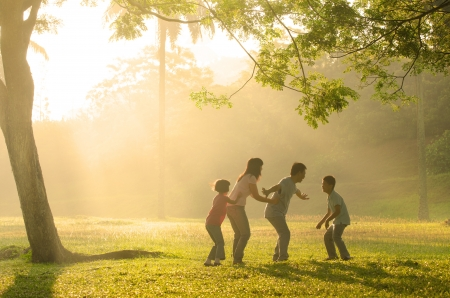 backlights: chinese family having quality time playing at outdoor park