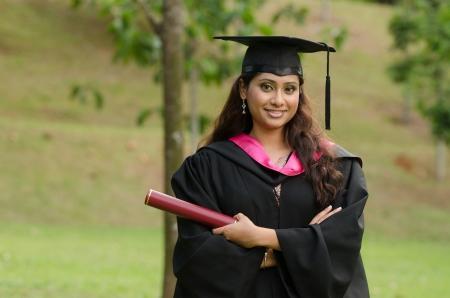 graduacion de universidad: sur asiático graduado femenino con el fondo verde Foto de archivo