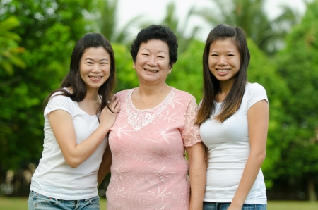 70s adult: chinese daughter and mother on green outdoor Stock Photo