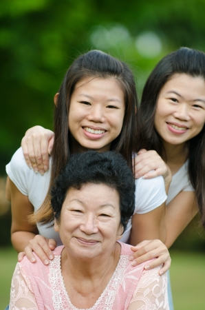grown ups: chinese daughter and mother on green outdoor Stock Photo
