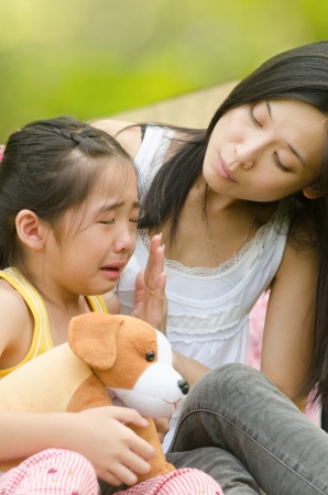argue kid: asian chinese girl crying while being comfort by her mother, outdoor background